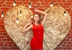 Charming woman in red dress on golden heart in studio. Charming elegant woman in a red dress on a background of a golden heart in the studio Stock Image