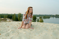 Charming emotional woman on sand near town lake Stock Photography