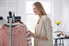 Charming energetic businesswoman placing garments in showroom. Trendy showroom. Pretty nice businesswoman calculating garment on stand while smiling Royalty Free Stock Images
