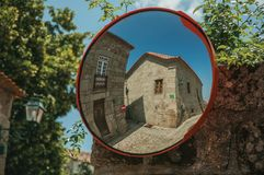 Old houses on cobblestone square reflected in street mirror. Charming facade of old houses on cobblestone square, reflected in street mirror at Linhares da Beira stock photography