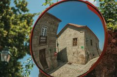 Old houses on cobblestone square reflected in street mirror. Charming facade of old houses on cobblestone square, reflected in street mirror at Linhares da Beira royalty free stock photography