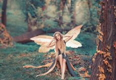 Charming fairy woke up in forest, sweetly smacks after sleeping, cue girl with blond hair, eyes closed in long green stock photo