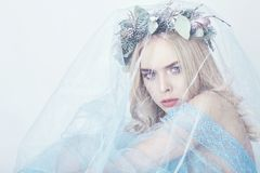 Charming fairy woman in a blue ethereal dress and a wreath on her head on white background, gentle mysterious blonde girl royalty free stock image