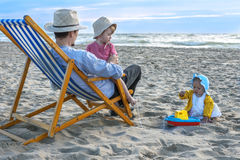 Charming family at the beach. Father enjoying a summer evening at the beach with his children Stock Photo