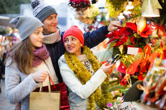 Charming family of three choosing Christmas star flower Stock Photography