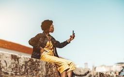 Black girl outdoors with a cellphone stock photo