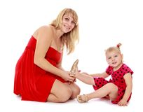 Charming fashionable mom puts on her little shoes Royalty Free Stock Photos