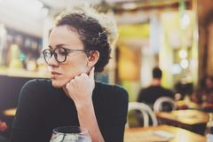 Charming fashionable woman with eyes glasses in a black sweater sits at a table in a cafe at night. Bokeh and flares. Effect on blurred background Stock Photo