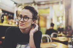 Charming fashionable woman with eyes glasses in a black sweater sits at a table in a cafe at night. Bokeh and flares. Effect on blurred background Stock Image