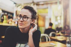 Charming fashionable woman with eyes glasses in a black sweater sits at a table in a cafe at night. Bokeh and flares. Effect on blurred background Royalty Free Stock Photos