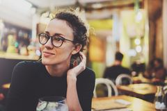 Charming fashionable woman with eyes glasses in a black sweater sits at a table in a cafe at night. Bokeh and flares. Effect on blurred background Royalty Free Stock Photography