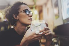 Charming fashionable woman with eyes glasses in a black sweater sits at a table in a cafe at night. Bokeh and flares. Effect on blurred background Stock Photos