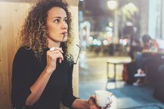 Charming fashionable woman with eyes glasses in a black sweater sits at a table in a cafe at night and reading book. Blurred background Royalty Free Stock Images