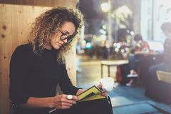 Charming fashionable woman with eyes glasses in a black sweater sits at a table in a cafe at night and reading book. Blurred background Stock Photos
