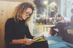 Charming fashionable woman with eyes glasses in a black sweater sits at a table in a cafe at night and reading book. Blurred background Stock Photography