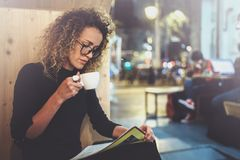 Charming fashionable woman with eyes glasses in a black sweater sits at a table in a cafe at night and reading book. Blurred background Stock Image