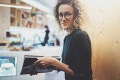 Charming fashionable woman with eyes glasses reading magazine sitting indoor in urban cafe.Casual portrait of pretty. Girl. Blurred background Royalty Free Stock Photo