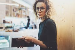 Charming fashionable woman with eyes glasses reading magazine sitting indoor in urban cafe.Casual portrait of pretty. Girl. Blurred background Stock Photography