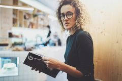 Charming fashionable woman with eyes glasses reading magazine sitting indoor in urban cafe.Casual portrait of pretty. Girl. Blurred background Royalty Free Stock Photography