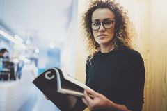 Charming fashionable woman with eyes glasses reading magazine sitting indoor in urban cafe.Casual portrait of pretty. Girl. Blurred background Stock Images