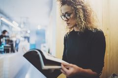 Charming fashionable woman with eyes glasses reading magazine sitting indoor in urban cafe.Casual portrait of pretty. Girl. Blurred background Royalty Free Stock Image