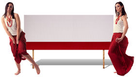 Charming fashionable woman presenting product. Collage. Attractive, charming young woman in motion next to empty red table. She is funny and happy, dressed in Royalty Free Stock Photography