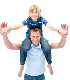 Charming father giving his son piggyback ride. Against a white background Royalty Free Stock Image