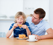 Charming father and his son eating waffles Stock Image