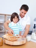 Charming father and his son spreading jam on bread Stock Photos