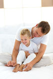 Charming father playing with his boy on a bed Royalty Free Stock Photos