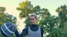 Charming female basketball player walking and playing with ball, park with blue sky above in background, low angle.  stock video