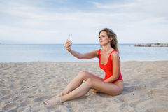 Charming female in fashion red swimsuit taking a picture of herself on smart phone Stock Photography