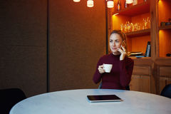 Charming female having mobile phone conversation in cafe while sitting against background with copy space area for text, Stock Images