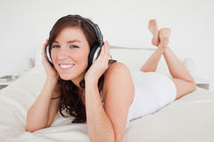Charming female with headphones lying Stock Photo
