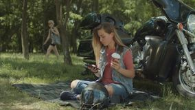 Charming female networking with cellphone outdoor. Beautiful stylish young female networking with smart phone and drinking coffee while relaxing on blanket by stock footage