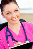 Charming female nurse holding a clipboard Stock Photo