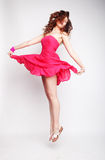 Charming female in pink dress jumping Royalty Free Stock Image