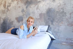 Charming female posing on camera with phone in hand and lying on. Slender girl smiles and looks into camera lens with gadget, cell in hand, lying on a large and Royalty Free Stock Photo