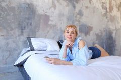 Charming female posing on camera with phone in hand and lying on. Slender girl smiles and looks into camera lens with gadget, cell in hand, lying on a large and Royalty Free Stock Images