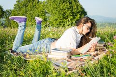 Charming female reading a book outdoors. And  taking notes while lying down Stock Photo