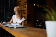 Charming female student preparing for lectures while sitting in bar, attractive hipster girl relaxing in restaurant during lunch Stock Image