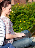 Charming female student using a laptop bo. Charming female student using a laptop and sitting behind her boyfriend in the park of their university Stock Photo