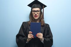 Charming female student wearing black mantle and standing with diploma in hands royalty free stock photos