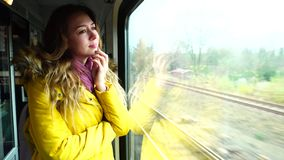 Charming female voyager sad that leaves and stands on  train near large transport window in  autumn afternoon. Alluring girl travels in train, makes sad face stock footage
