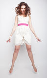 Charming female in white dress jumping over grey background Royalty Free Stock Images