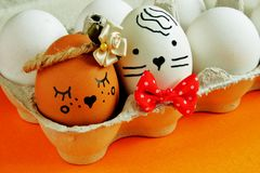 Charming flirty light brown egg with satin flower and elegant white egg with red bow tie in carton box on bright orange background royalty free stock photos
