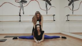 Charming focused young woman doing split twine and stretching with trainer, group of girl with instructor yoga class. Charming focused young woman doing split stock video footage