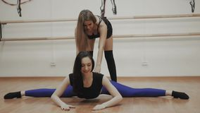 Charming focused young woman doing split twine and stretching with trainer, group of girl with instructor yoga class. Charming focused young woman doing split stock footage