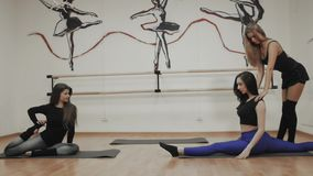 Charming focused young woman doing split twine and stretching with trainer, group of girl with instructor yoga class. Charming focused young woman doing split stock video