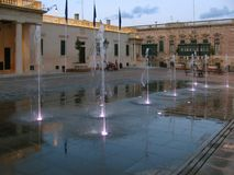 Small fountains in the square. Malta. Valletta. Charming fountains decorate the square in front of the sunset in front of the government building in the evening Stock Photos